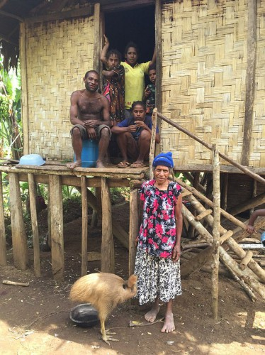 A family of rainforest landowners from Numba, with their house and a pet cassowary.