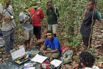 Luda Paul (centre) setting up equipment for point count survey of birds.