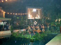 Opening ceremony for the Swire Research Station, when a cultural group is dancing on a platform floating in a pool of the Gateway Hotel in Port Moresby, under the image of the Wanang conservation leader Filip Damen projected on the screen.